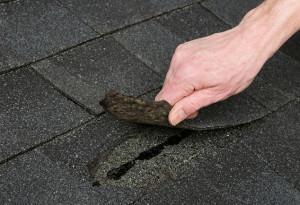 Dakdekker bekijkt de scheur in het dak