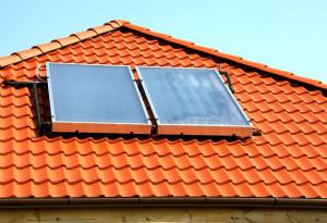 Schuin dak met oranje dakpannen en twee zonnepanelen